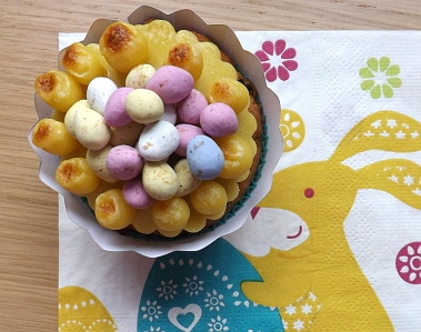 overhead of a simnel cupcake with mini eggs on top
