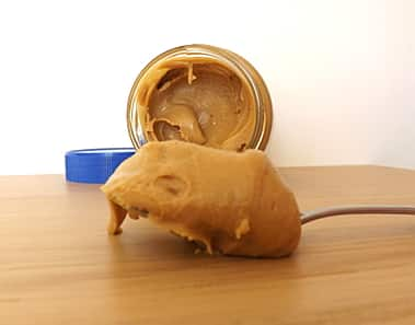 a spoonful of peanut butter with an open jar in the background