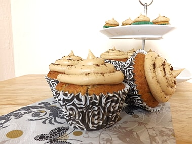close up of three cupcakes with a cake stand in the backround