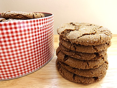 a stack of cookies next to a cookie tin