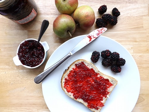 Blackberry and apple jam spread on bread and butter