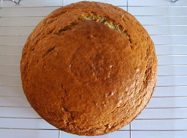 a baked banana cake cooling on a rack