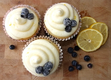 3 lemon and blueberry cupcakes with slices of lemon and bluberries