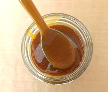 arial shot of caramel sauce in a jar with a spoon