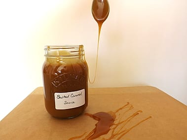 Salted caramel sauce being spooned out of the jar