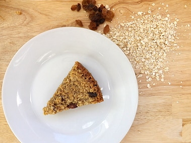 A flapjack on a plate with some sultanas and oats