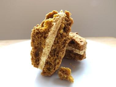 a whoppie pie cut in half to see the spiced pumpkin buttercream