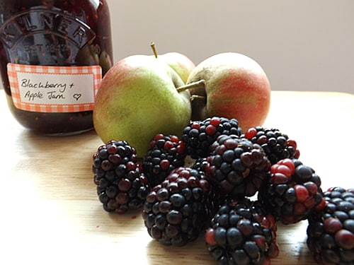 fresh blackberries and apples with a jar of jam