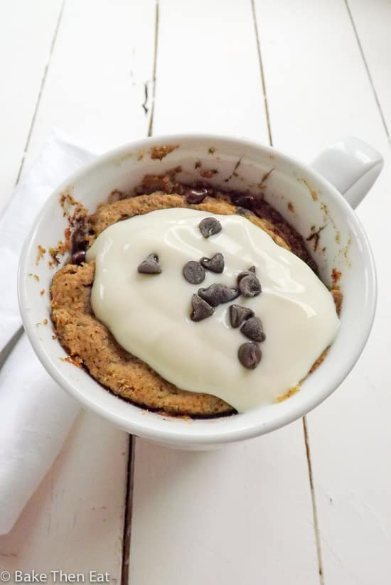 Gluten Free Vegan Banana Mug Cake with yogurt and mini chocolate chips topping it. | BakeThenEat.com