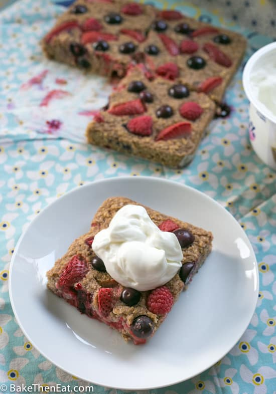 A slice of Healthy Baked Mixed Berry Oatmeal served with Greek yoghurt | BakeThenEat.com