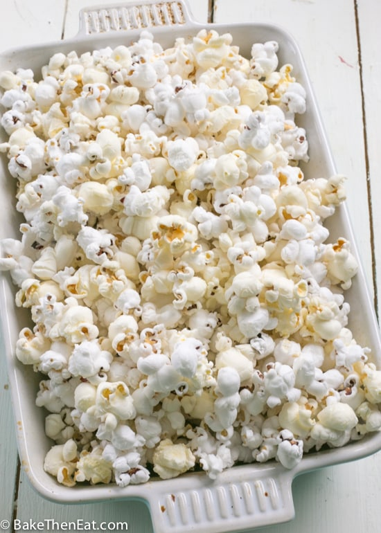 A big tray of popcorn ready to be made into Homemade Cookies n Cream Popcorn | BakeThenEat.com