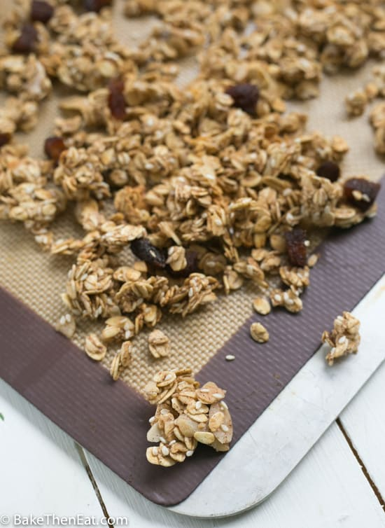 Easy Homemade Honey Almond Granola spread out on the baking sheet | BakeThenEat.com