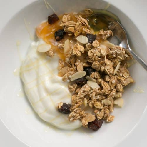 A bowl of easy homemade honey almond granola with Greek yogurt and homey | BakeThenEat.com