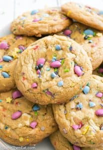 Unicorn Sprinkle White Chocolate Chip Cookies stacked up on a plate | BakeThenEat.com