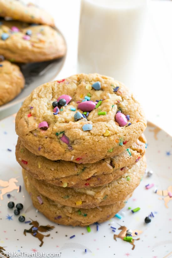 Unicorn Sprinkle White Chocolate Chip Cookies sucked up on a plate | BakeThenEat.com