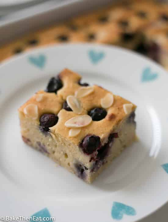 A slice of Cannellini Bean Blueberry Almond Tray on a plate | BakeThenEat.com