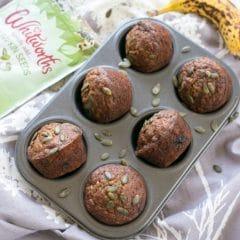 A pan of Pumpkin Seed Brown Sugar Banana Muffins with pumpkin seeds and a ripe banana   BakeThenEat.com