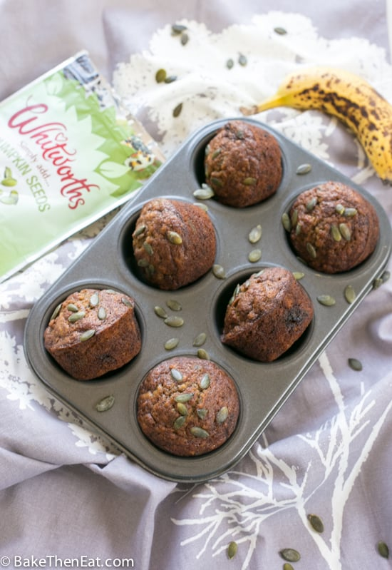 A pan of Pumpkin Seed Brown Sugar Banana Muffins with pumpkin seeds and a ripe banana | BakeThenEat.com