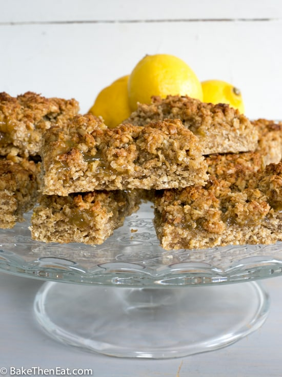 Zesty lemon flapjacks piled up on a cake plate | BakeThenEat.com